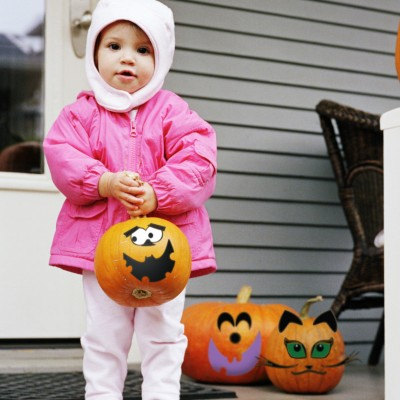 Little Girl Surrounded by Pumpkin Faces