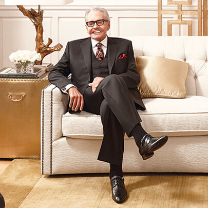 Art Van Elslander dressed in a suit and tie sitting on a white fabric couch