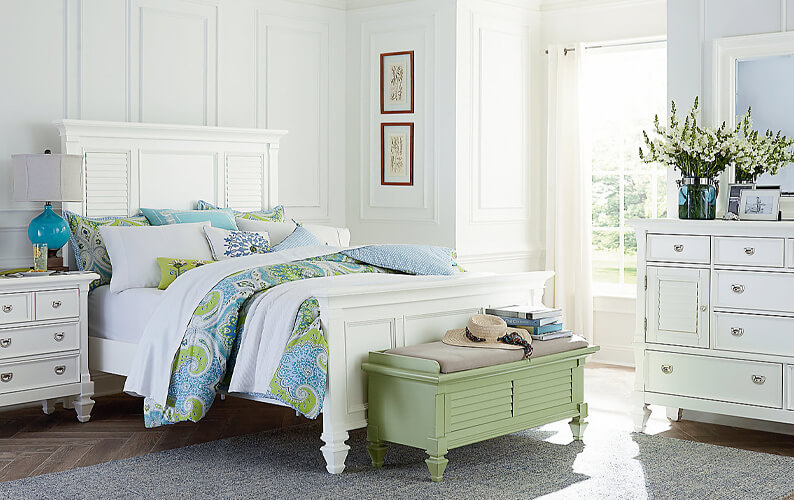 Shabby chic white bedroom set with light green and blue bedding and a green storage chest