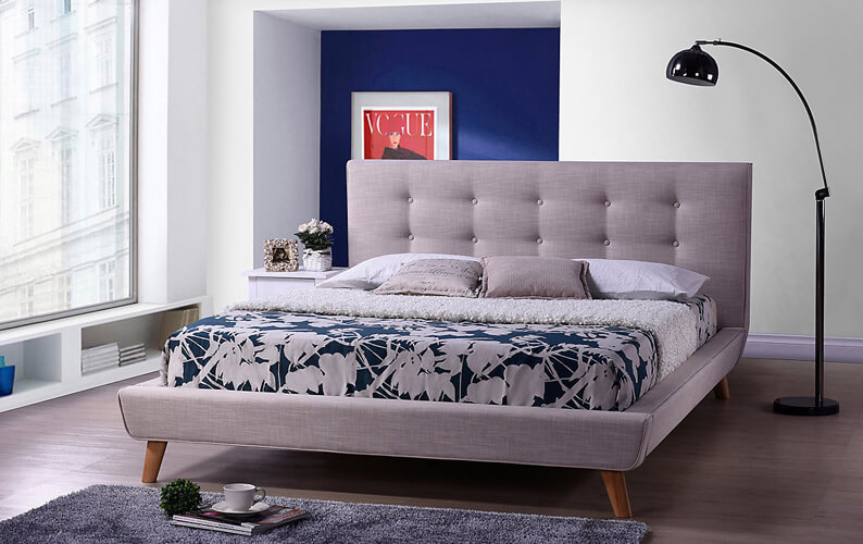 Mid-century modern upholstered gray bed with hairpin legs next to a floor lamp against a white wall with a dark blue painted alcove