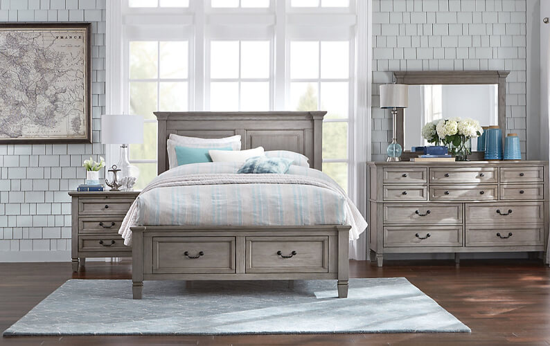 Light gray wood bedroom set featuring a bed, nightstand and dresser with mirror with dark metallic hardware atop a light blue area rug