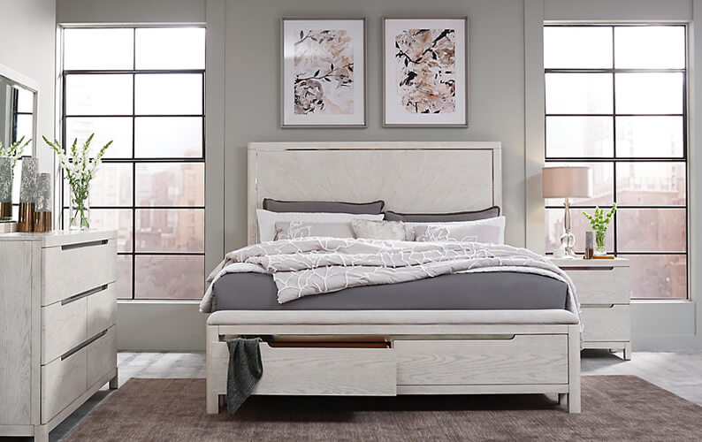 Room featuring white natural grain wood bed with storage drawers, gray and white bedding, a matching dresser and nightstand, and floral wall art prints hanging above the bed