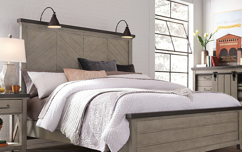 Farmhouse bedroom with a natural wood bedroom furniture, cream colored bedding, and a chevron headboard with attached lamps