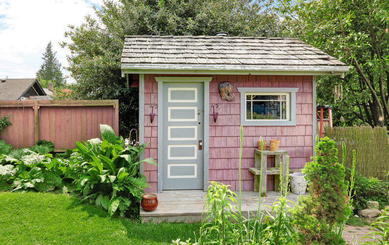 Rose colored she shed with shingles and a pale green door surrounded by greenery