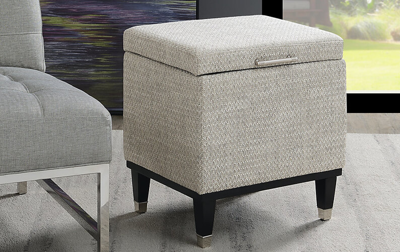 Small gray storage ottoman with black legs with silver bases