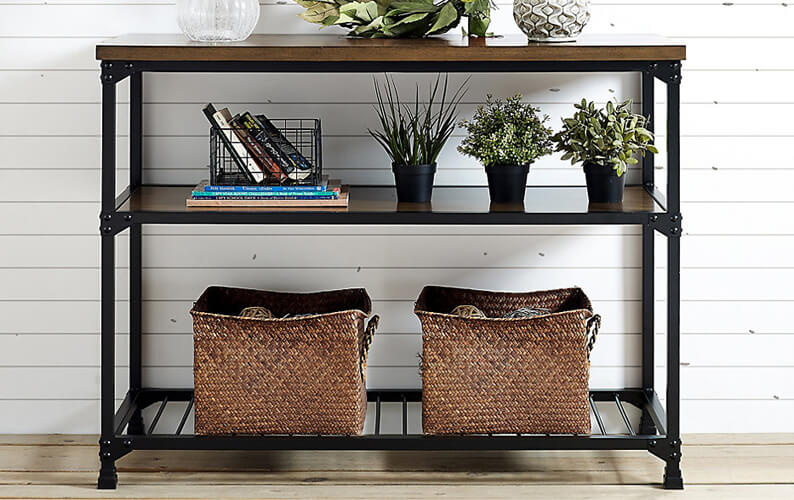 Wood and black metallic sofa table with storage baskets and decorative plants