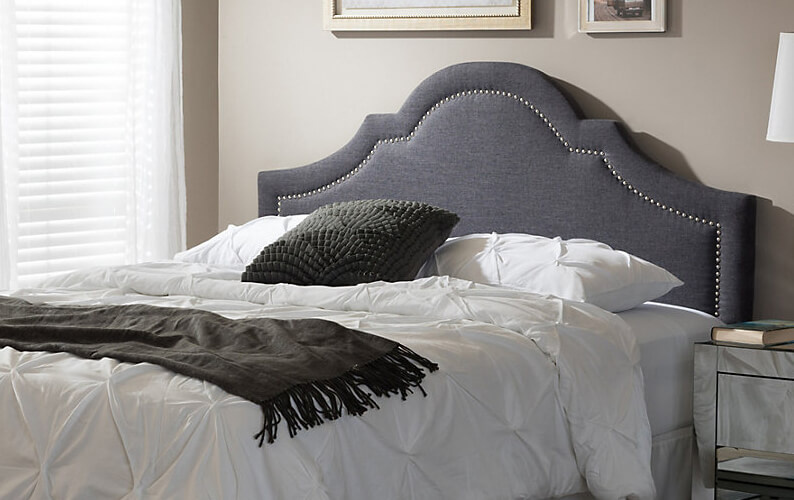 Bed with gray upholstered headboard with nailhead trim