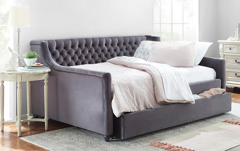 Dark gray upholstered daybed with trundle featuring button tufting and cream-colored bedding