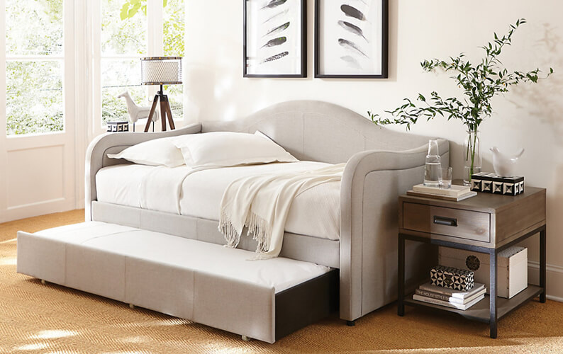 Beige daybed with trundle next to wood end table with decorative accents