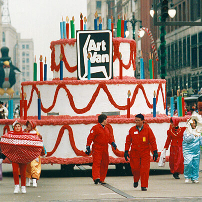 Art Van parade float in the shape of a large cake with people dressed in costume walking in front for the Detroit Thanksgiving Day Parade