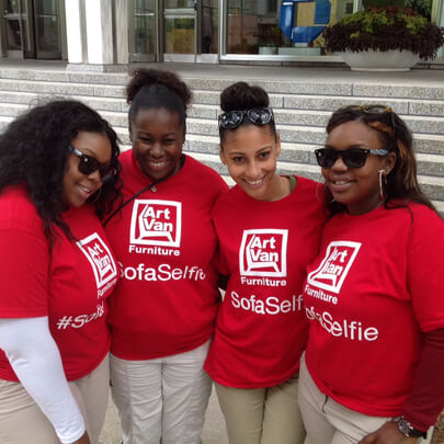 "Four women wearing red t-shirts with ""#SofaSelfie"" and the Art Van logo printed on them"