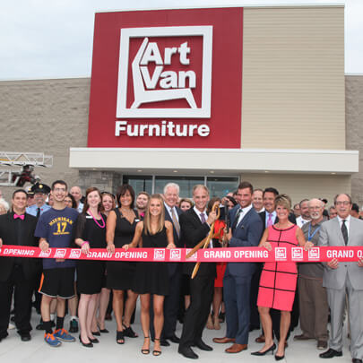 Two men dressed in suits holding giant scissors in front of a crowd of people at an Art Van Furniture store ribbon cutting ceremony