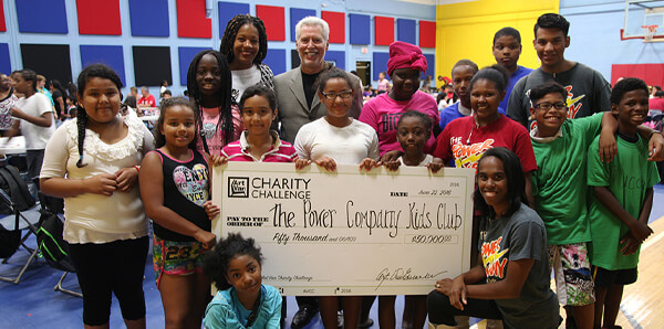 A group of children and adults holding a giant check from the Art Van Charity Challenge