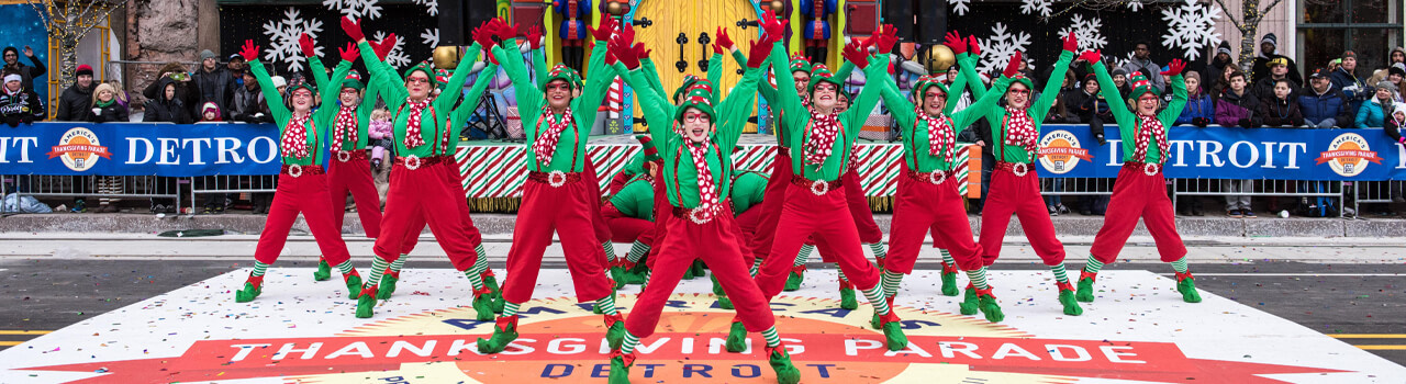 Dancing troupe dressed in green and red with arms outstretched at the Thanksgiving Parade in Detroit