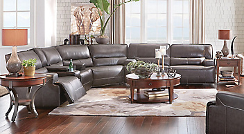 Brown reclining sectional with circular wood coffee and end tables and a light colored area rug