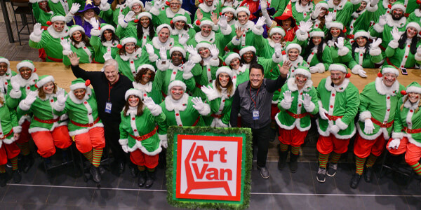 The Art Van Santa Parade with a large group of men and women dressed in green and red Santa outfits