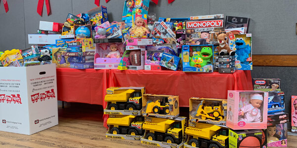 A table full of toys and games with more toys lined up in front next to a Toys for Tots donation box