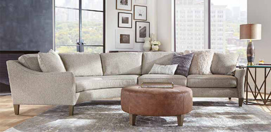 Living room with off-white couch, leather circle ottoman, and side table with lamp atop a grey area rug