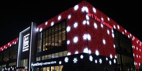 Exterior of Art Van Furniture in Warren brightly lit in red with white snowflakes for the Wonderland Lighting event